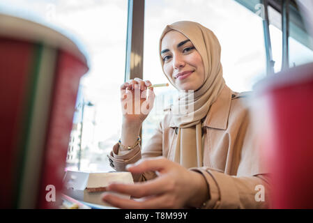 Beautiful Muslim woman in headscarf and fashionable modern trendy clothes eats big hamburger in restaurant .Modern Muslim woman lifestyle or business  - Stock Photo