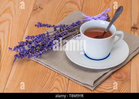 tea in a white cup and a bunch of dried lavender on a linen napkin close-up - Stock Photo