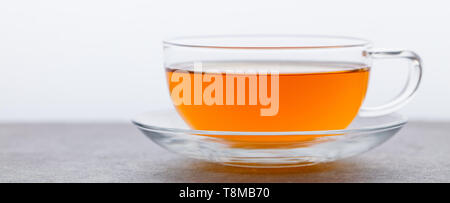 Tea in glass cup. Grey background. Copy space. - Stock Photo