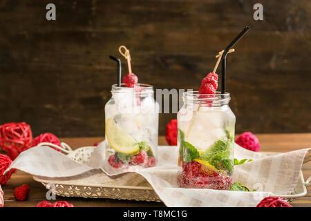 Mason jars of fresh raspberry lemonade on tray - Stock Photo