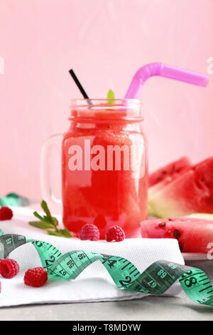 Mason jar of tasty red smoothie with ingredients and measuring tape on grey table. Diet concept - Stock Photo