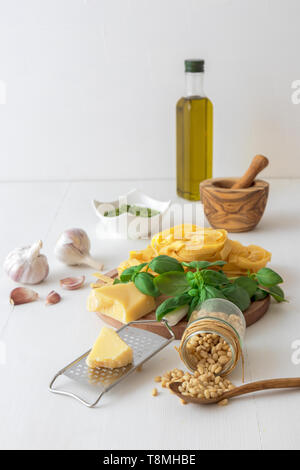Making pesto. The table with ingredients to produce basil pesto. Mortar, fresh basil herbs, pine nuts, olive oil, parmesan cheese, garlic, bowl with p - Stock Photo