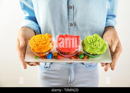Woman holding plate with tasty colorful cupcakes and candies on light background, closeup - Stock Photo