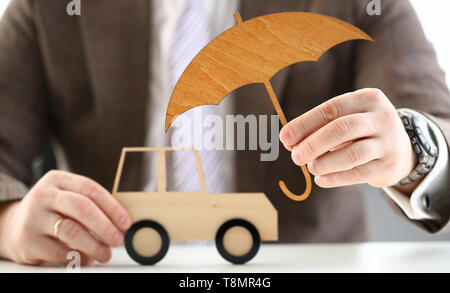 Male hand hold wooden umbrella aganist - Stock Photo
