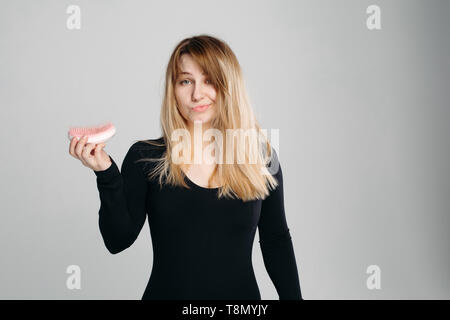 Close up portrait of young confused girl with messy blonde hair. - Stock Photo