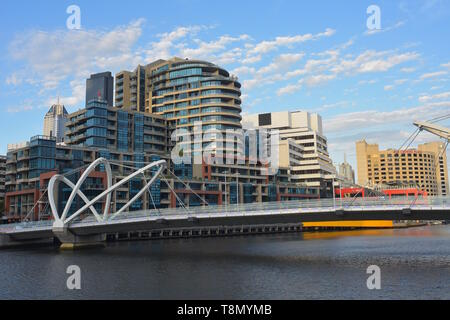Pedestrian Seafarers Bridge connecting banks of Yarra River in Melbourne with modern architecture in background. - Stock Photo