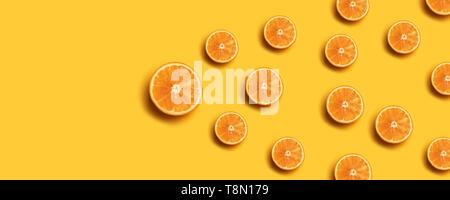 Fruit pattern of fresh orange slices on yellow background. - Stock Photo