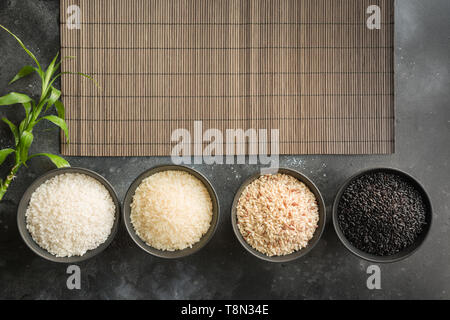 Different varieties of rice in bowls. Top view. Black background. Space for text. - Stock Photo