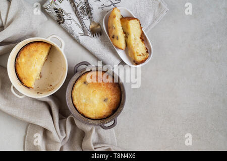 Two pans with cottage cheese casserole and slices of casseroles in a plate on gray table. Top view - Stock Photo