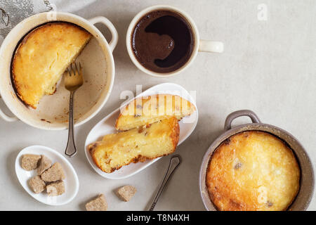 Two pans with cottage cheese casserole, slices of casseroles in a plate and cup of coffee on gray table. Top view - Stock Photo