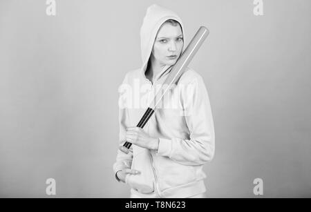 Girl troublemaker. Woman play baseball game or going to beat someone. Girl hooded jacket hold baseball bat blue background. Woman in baseball sport. Baseball female player concept. She is dangerous. - Stock Photo