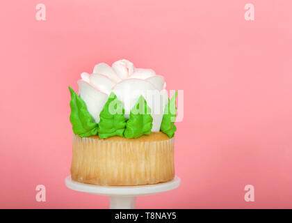Close up on large cup cake with giant frosting rose sitting on white pedestal on wood table. Simple design with copy space for Mother's Day, Valentine - Stock Photo