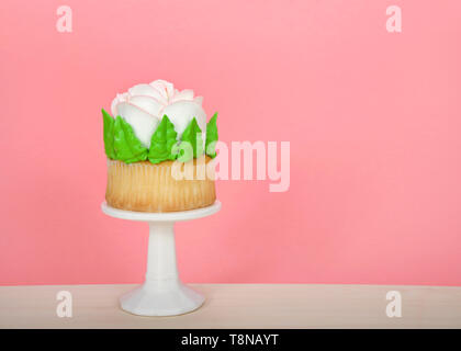 Large cup cake with giant frosting rose sitting on white pedestal on wood table. Simple design with copy space for Mother's Day, Valentine's Day, Quin - Stock Photo