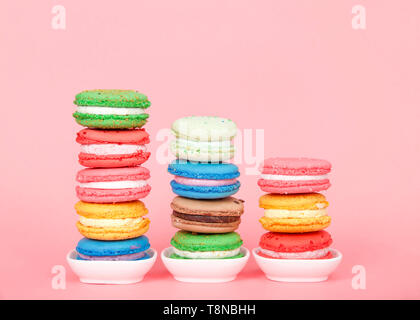 Macaron cookies in tiny white dishes stacked in graduated rows, colorful traditional french pastry on a pink background. - Stock Photo