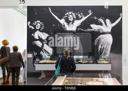 View of a woman looking at a large photographic image of three joyful dancing women in an exhibition of Secession art in the Leopold Museum, Vienna. - Stock Photo