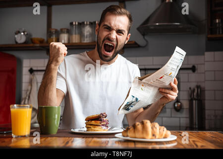 Angry shocked man having breakfast, reading newspaper - Stock Photo
