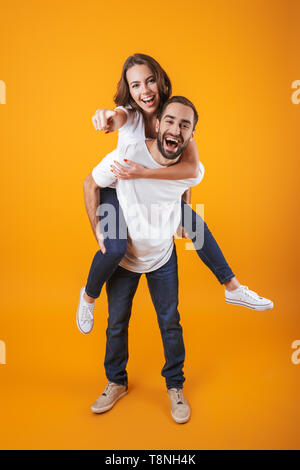 Full length image of young couple having fun while man piggybacking woman isolated over yellow background - Stock Photo