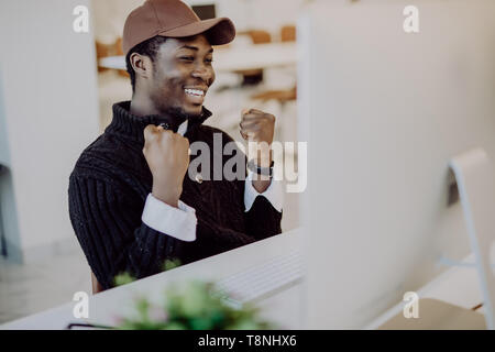 Happy african-american businessman in suit looking at laptop excited by good news online, black man winner sitting at office desk achieved goal raisin - Stock Photo