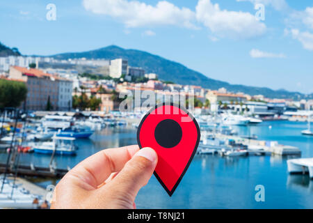 closeup of the hand of a young caucasian man with a red marker pointing the Port of Ajaccio, in Corsica, France - Stock Photo
