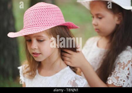 girl braids her friend's braid in park - Stock Photo