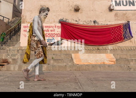 Sadhu (holy man) covered in ashes walks along the ghats of the River Ganges, Vranasi, India - Stock Photo