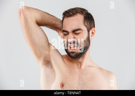 Close up portrait of a disgusted bearded man standing isolated over white background, smelling his armpit - Stock Photo