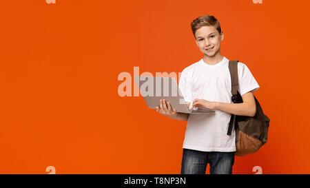 Teenage boy with backpack using laptop, orange background - Stock Photo