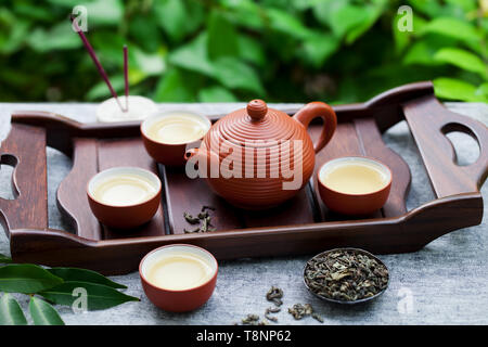 Green tea in tea pot and bowls, cups on a wooden tray. Outdoor background. - Stock Photo