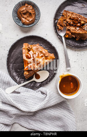 Pieces of homemade snickers cake with chocolate cream and caramel on a black saucer, white background, top view. - Stock Photo