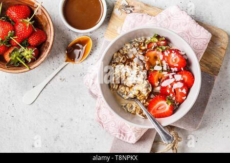 Vegan breakfast. Oatmeal with chia seeds, berries, seeds and caramel in a white bowl. - Stock Photo
