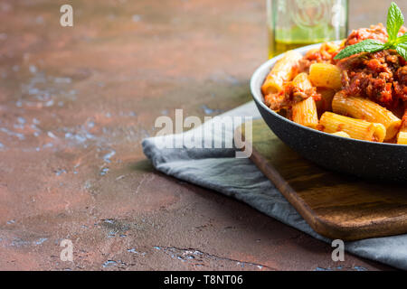 Delicious rigatoni pasta with italian tomato meat ragu sauce served in a pan on dark brown background. Traditional pasta dish concept. Home made lunch - Stock Photo
