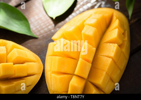 Fresh ripe mango fruit cut into cubes on wooden table background. Closeup view. Healthy vegetarian tropical fruit - Stock Photo