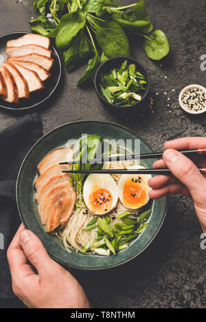 Eating japanese ramen noodle soup with chicken. Hand holding chopsticks above bowl of asian soup. Black concrete background - Stock Photo