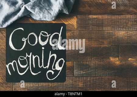 Good morning greeting on blackboard on a wooden table background. Cheerful morning greeting. Design mock up - Stock Photo