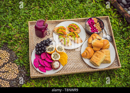 Breakfast on a tray with fruit, buns, avocado sandwiches, smoothie bowl standing on the grass - Stock Photo