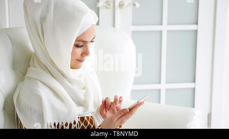 Portrait of young muslim woman in white hijab and traditional dress is browsing internet pages in smartphone sitting on the sofa, side view. copyspace - Stock Photo