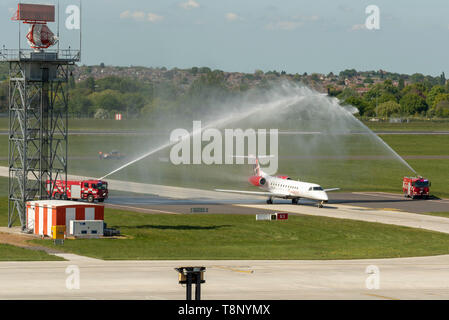 Loganair Embraer ERJ135 at London Southend Airport, Essex, UK. Traditional water arch salute supplied by the airport's fire trucks welcoming launch - Stock Photo