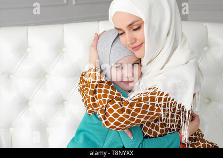 Muslim family mom and her little daughter in hijabs are hugging sitting on the sofa at home in modern white interior, side view. - Stock Photo