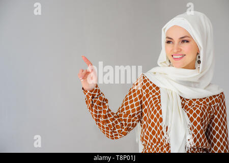 Portrait of gorgeous arab woman in headscarf pointing finger at copy space isolated over gray background - Stock Photo