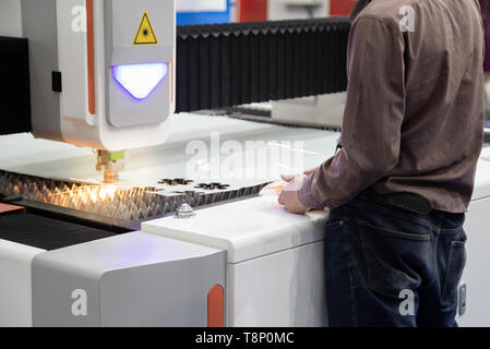 Industrial worker operate CNC laser cutting machine cutting metal sheet - Stock Photo
