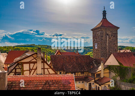 Lovely panoramic rooftop view of the medieval town Rothenburg ob der Tauber in the Franconia region of Bavaria, Germany. Between half-timbered houses... - Stock Photo