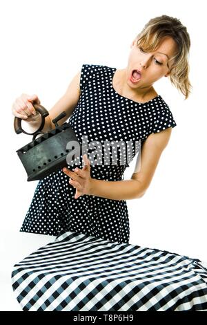 Attractive housewife in pin up style feels pain from hot vintage coal metal iron during ironing - high temperature tool - concept on white background - Stock Photo