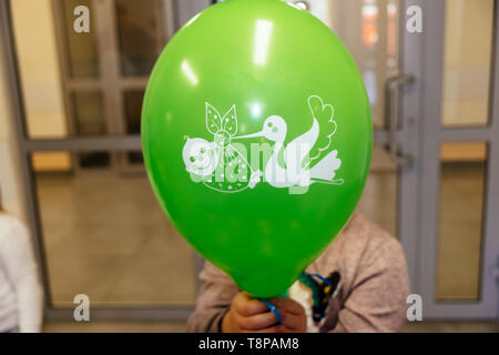girl holding a green ball in her hand with a drawing of a stork and a baby in the maternity hospital - Stock Photo
