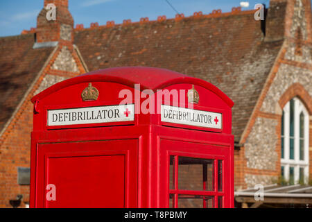 A bright red traditional public telephone box converted to house a community defibrillator in Peppard Common, Oxfordshire - Stock Photo