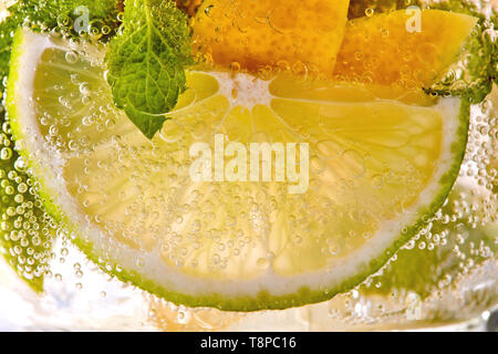 Macro photo of a summer mojito cocktail with slices of lime, lemon and mint leaves in a glass. - Stock Photo