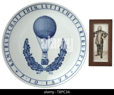 A Meissen wall plate of the airship troops White, glazed porcelain with cobalt blue decoration. In the centre the image of a balloon framed by oak leaves, the border with continuous inscription 'Kameradschaft ehem. Luftschiffertruppen 7.10.1896' (tr. 'Airship veterans group 7 October 1896'). The bottom with blue underglaze swords mark as well as press marks '135' and 'N 117'. Diameter circa 25 cm. Comes with a contemporary, framed photograph (13.5 x 6.5 cm) which shows the airship pilot who owned this plate. Very rare. historic, historical, troop, troops, armed forces, mili, Editorial-Use-Only - Stock Photo