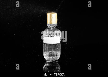 Pouring of water on bottle with perfume against black background - Stock Photo