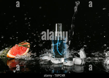 Pouring of water on bottle with perfume, ice cubes and grapefruit against black background - Stock Photo