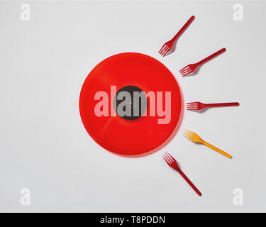 Red vinyl record with plastic colorfut forks on a gray background. - Stock Photo