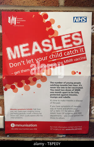 A poster with advice for patients about measles is seen in an NHS local doctors surgery waiting room in Warwickshire, UK, On May 14, 2019. - Stock Photo